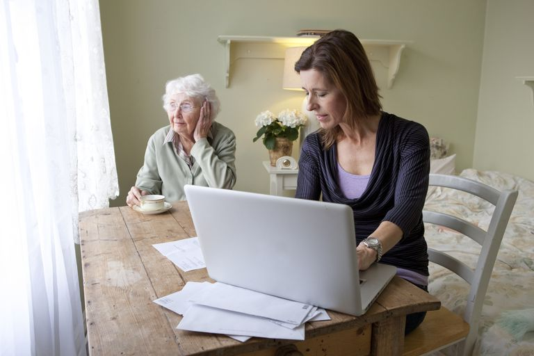 Woman reviewing bills for senior woman