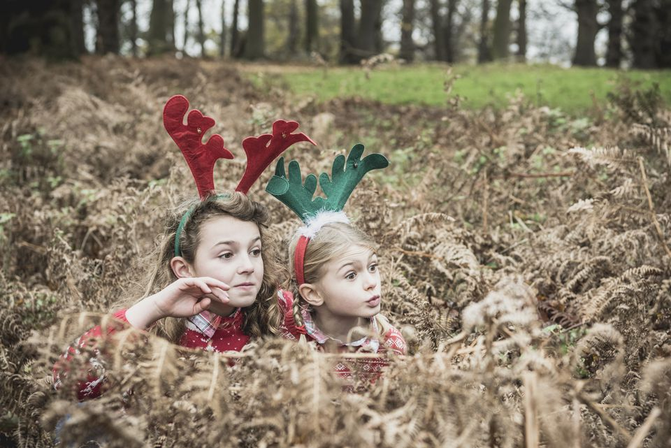 Two girls hiding in bracken wearing reindeer antlers