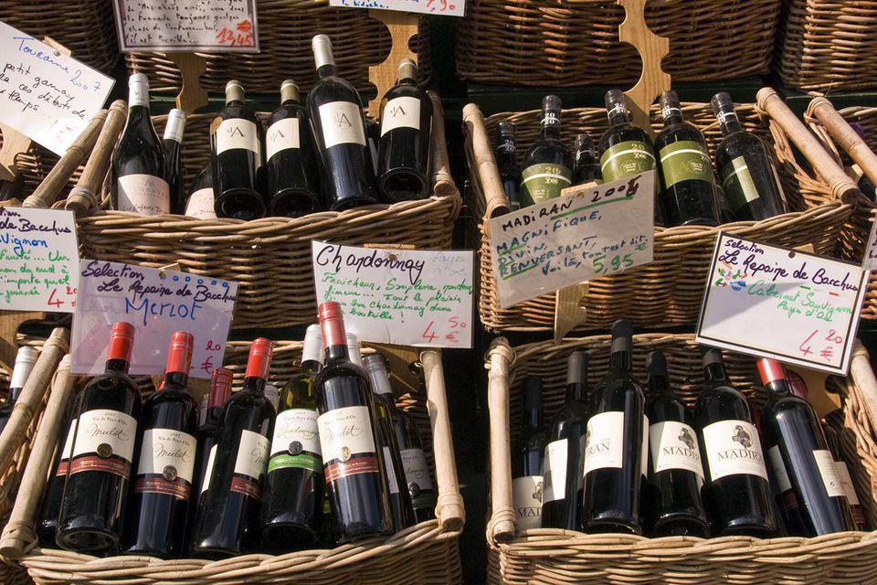 Wine shop in Rue Mouffetard displaying baskets of bottles.