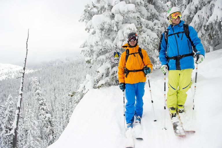 Two skiers smiling on top of steep powder run