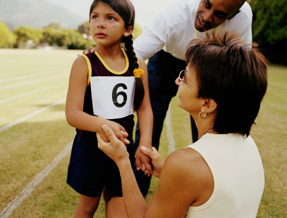 Girl (4-6) being comforted by mother and teacher at school sports day