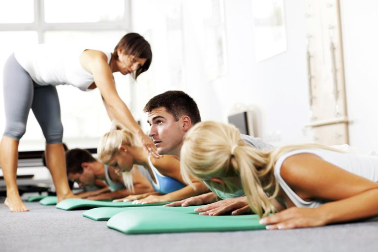 Group of young people doing Pilates exercises with the help of instructor.