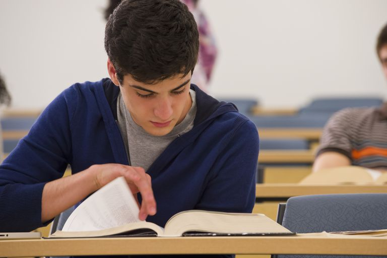 Student reading textbook in classroom
