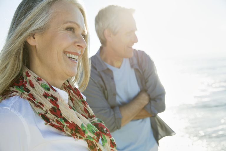 Cheerful mature couple looking at view on beach