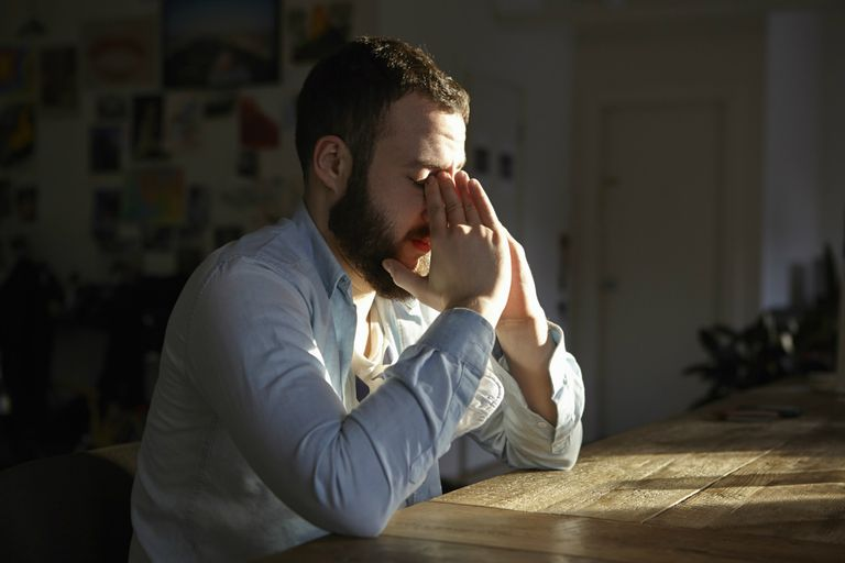 Man sitting at kitchen table with hands on face