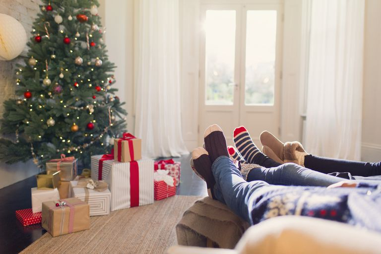 Relaxed family in socks with feet up near Christmas tree