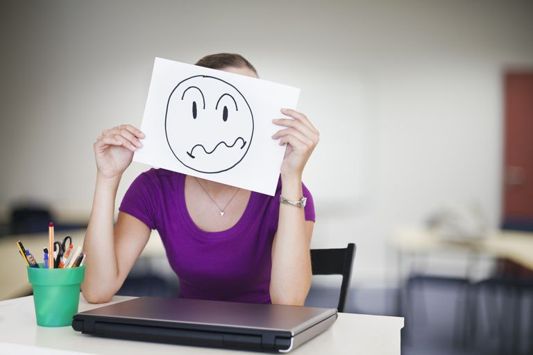 negative employee holds face frown picture over her face