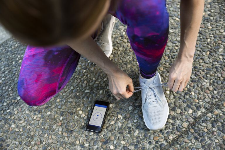 A runner crouching down to tie a shoe while checking a fitness app on a smartphone