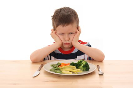A child who doesn't want to eat a plate full of vegetables.