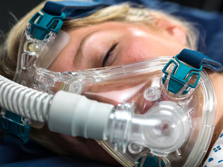 Close-up of a woman wearing a CPAP mask for sleep apnea.