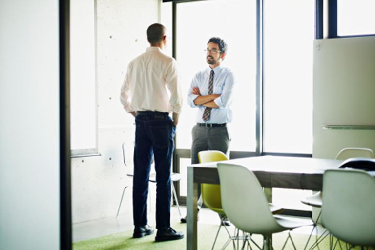 Two businessmen in discussion in conference room