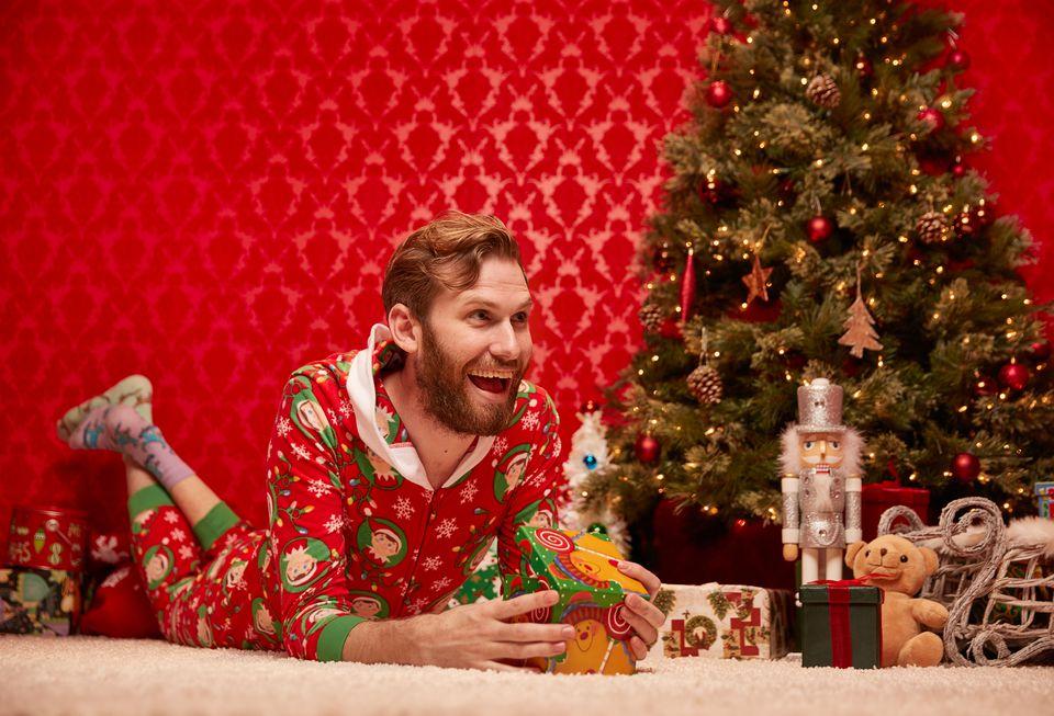 Lanky doofus in Christmas onesie opens gift.