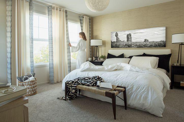 Woman in bathrobe at bedroom window
