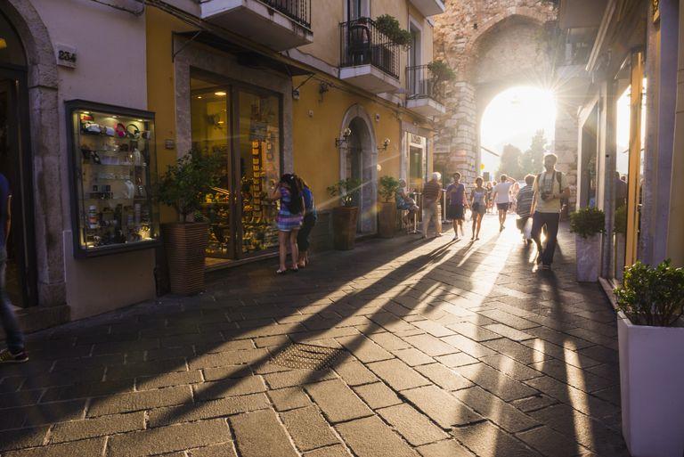 Tourists entering Corso Umberto, the main street in Taormina at sunset