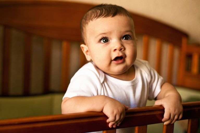 Baby boy standing in his crib.