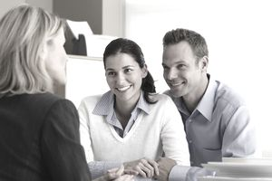 an adult couple talking with insurance agent in office, smiling