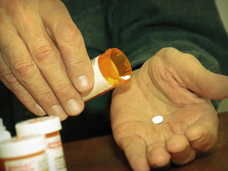 Man holding a pill bottle with a pill in his hand