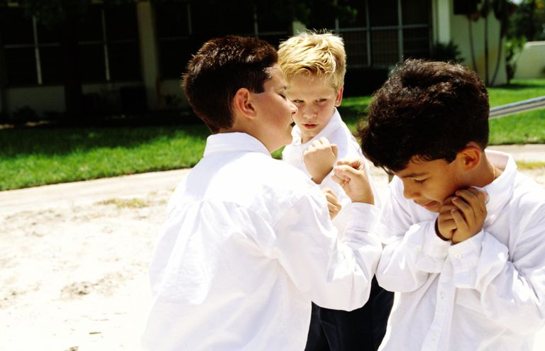Side profile of school boys (10-12) bullying a classmate in the yard