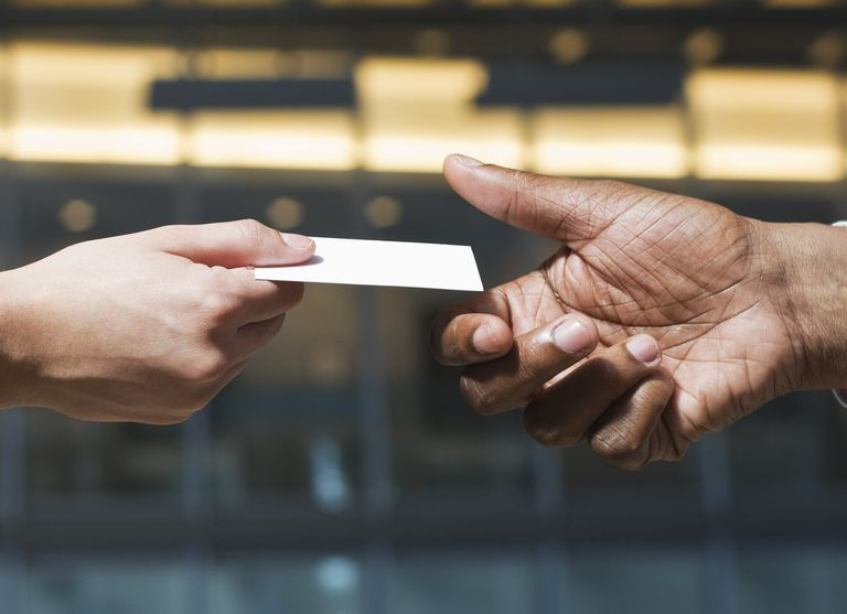 Close-up of hands passing business card