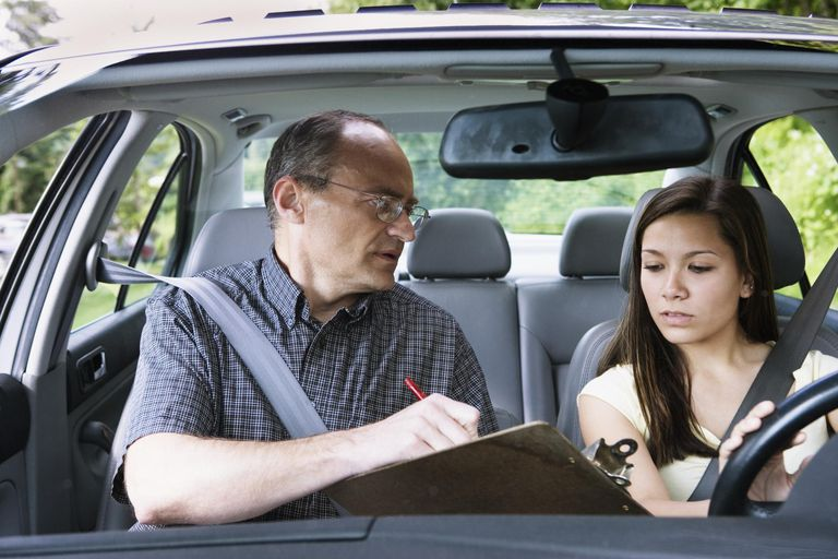 Teenage girl (14-16) sitting in car with driving instructor