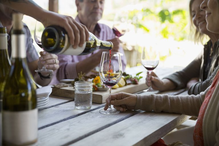 Couples wine tasting and enjoying charcuterie board on patio at winery tasting room
