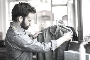 Male design professional analyzing shirt at studio