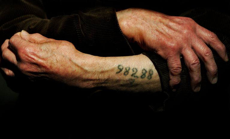 A Holocaust survivor showing his tattooed number.