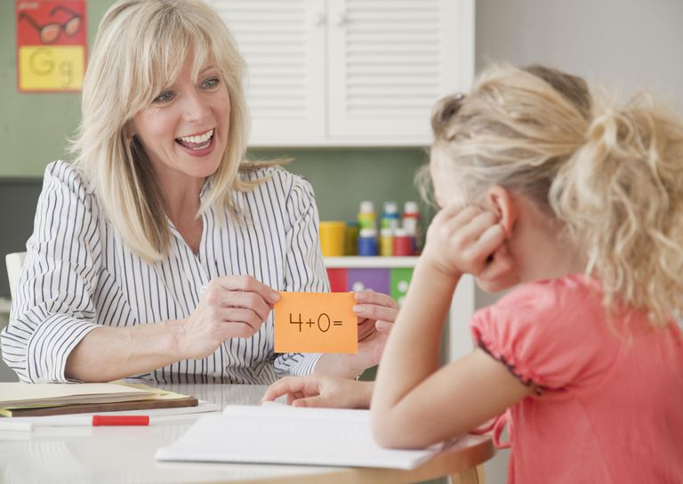 Teacher showing girl flash card, smiling