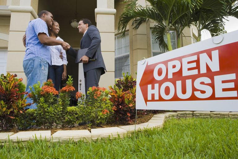 African couple shaking hands with Hispanic real estate agent