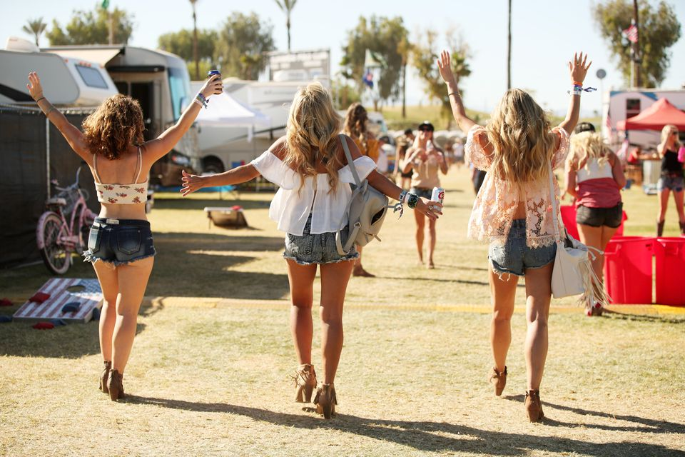 women at Stagecoach music festival walking next to RVs