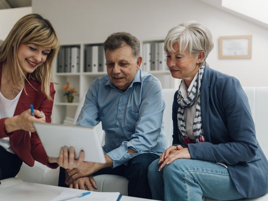 Senior Couple Meeting with Financial Advisor, selective focus to senior man and mature woman listening to financial advisor.