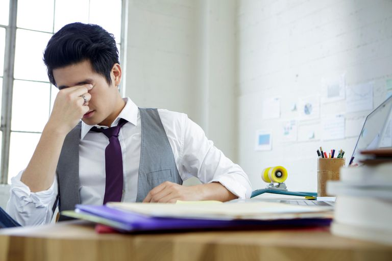 Stressed young man sitting at office desk