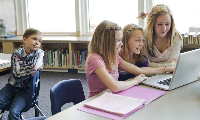 Teen girls ignoring another student in school.