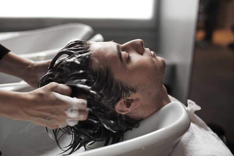 Man getting hair washed in sink at salon