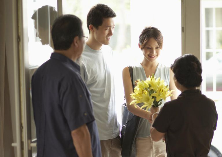 Parents greeting adult offspring at front door
