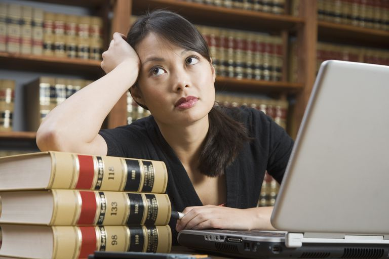 Asian woman leaning on stack of library books
