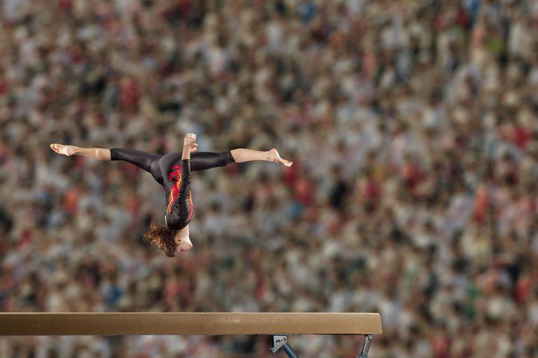 Hispanic gymnast in mid-air over balance beam