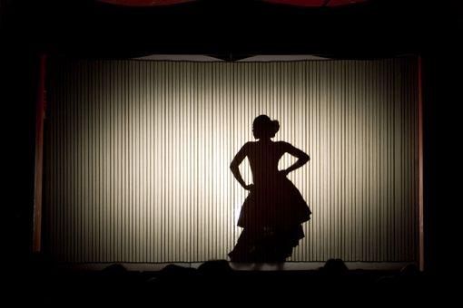 Salsa dancer at a performance behind curtian