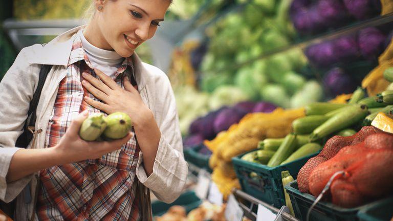Woman buying veggies in a supermarket. Zucchini