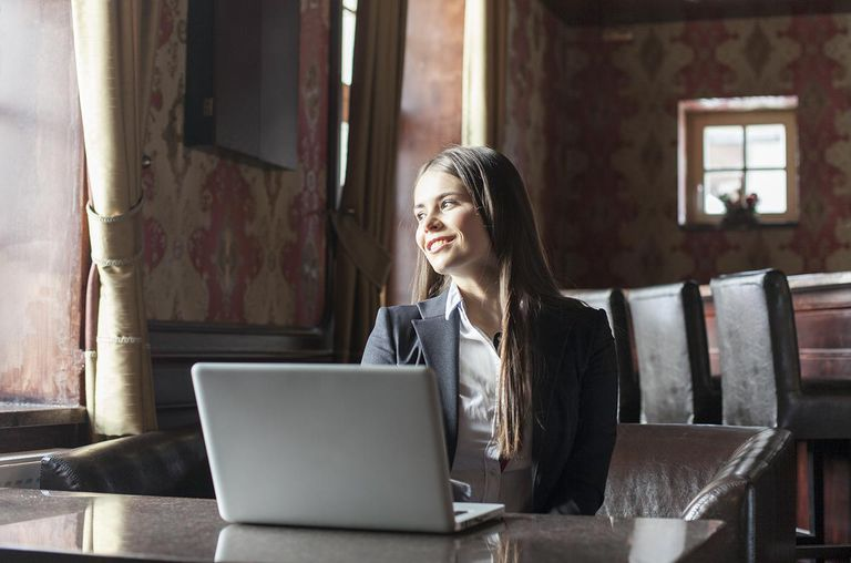 Smiling woman with laptop looking through window