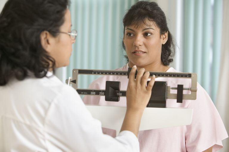 woman getting weighed on scale by doctor