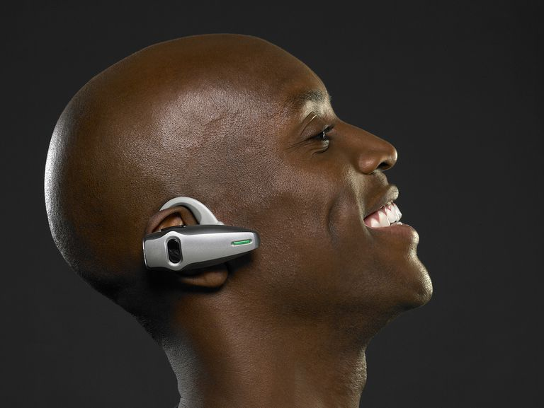 Man wearing hands free mobile phone device, side view, close-up.