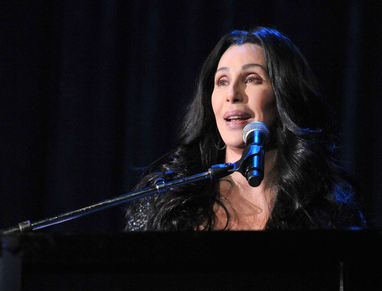 Cher sits at a piano and sings.