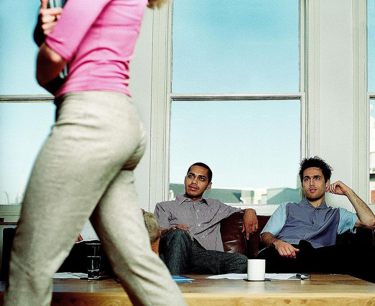 Three men watching woman walk past