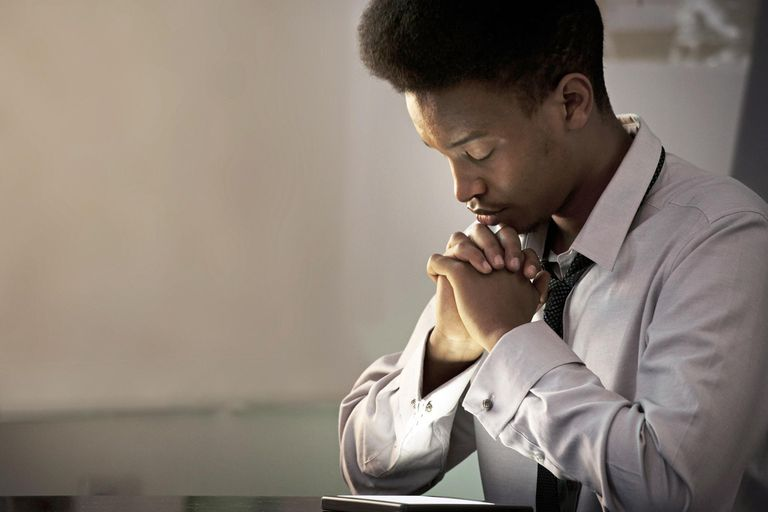 Young Black male businessman praying