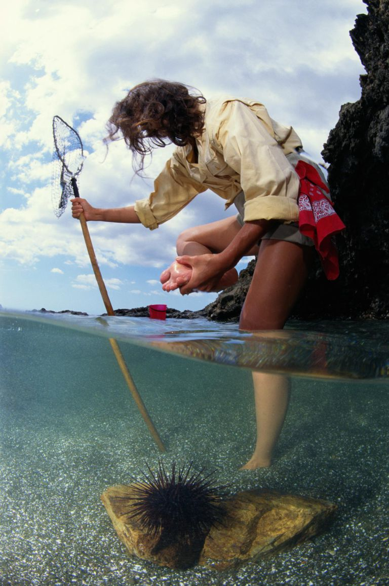 Woman leaning on fishing net holding foot, partial underwater view