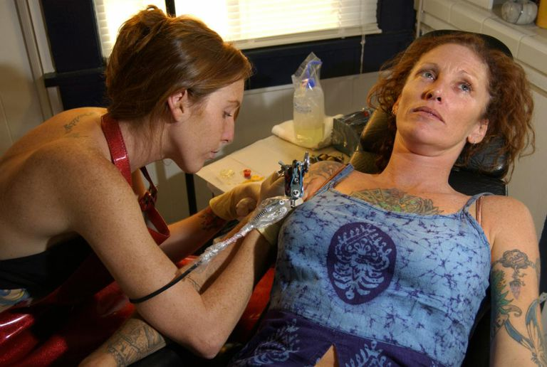 Woman getting tattoo
