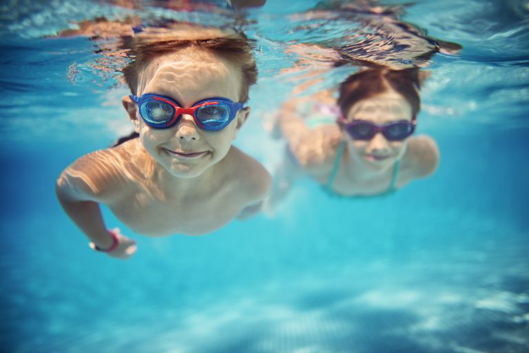 Happy Kids Swimming Underwater in Pool