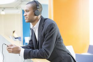 Businessman listening to headphones in office