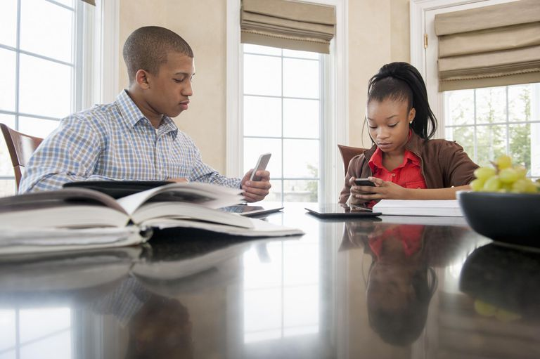 Teens at home with smartphones and school books